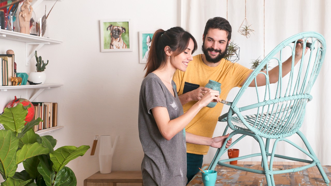 couple painting a chair