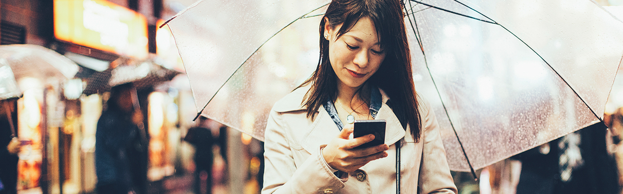 Woman using mobile under umbrella